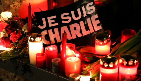 "Candles and a placard which reads ""I am Charlie"" are pictured as tributes to victims at the French embassy at Pariser Platz in Berlin January 7, 2015, following a shooting by gunmen at the offices of weekly satirical magazine Charlie Hebdo in Paris. Hooded gunmen stormed on Wednesday the Paris offices of Charlie Hebdo (Charlie Weekly) a weekly satirical magazine known for lampooning radical Islam, killing at least 12 people, including two police officers in the worst militant attack on French soil in recent decades. A police union official said the assailants remained at liberty and there were fears of further attacks. REUTERS/Fabrizio Bensch (GERMANY - Tags: CIVIL UNREST POLITICS CRIME LAW MEDIA)"