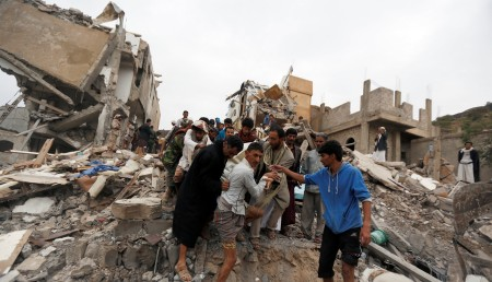 People carry the body of a woman they recovered from under the rubble of a house destroyed by a Saudi-led air strike in Sanaa