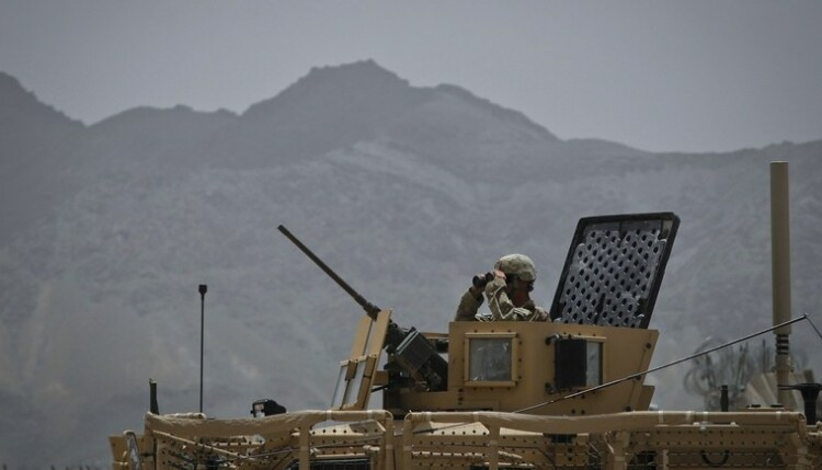 A soldier from the U.S. Army's 1st Battalion, 41st Infantry Regiment, Task Force Bulldog uses his binoculars at the turret of an armoured vehicle at Combat Outpost Boston in Kherwar district in Logar province